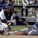 San Diego Padres' Rico Noel, right, slides safely past Milwaukee Brewers catcher Jonathan Lucroy for an inside-the-park home run during an exhibition spring training baseball game on Friday, March 7, 2014, in Phoenix The Associated Press