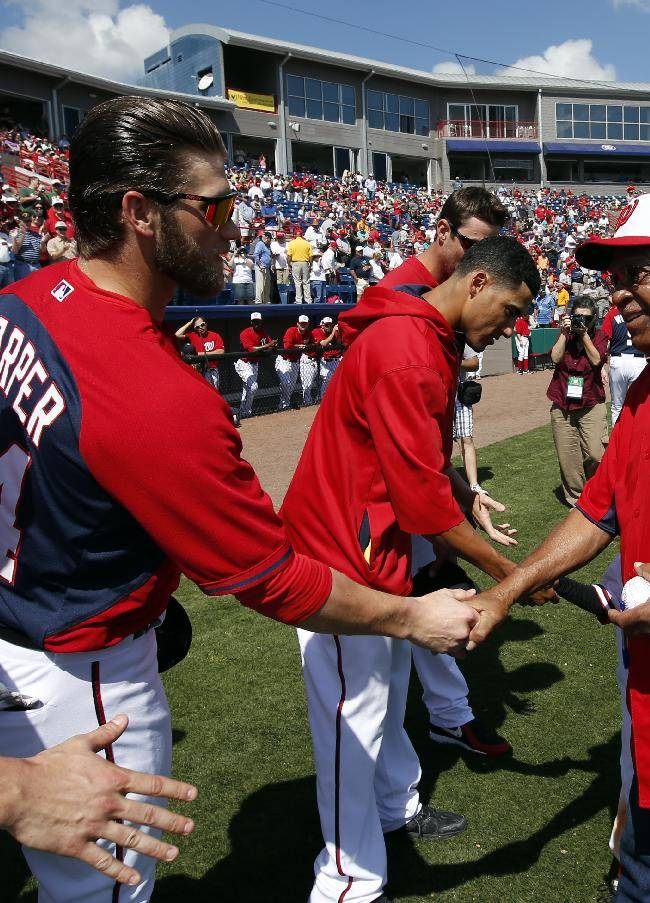 Washington Nationals' Bryce Harper (34) shakes hands with U.S. Army Sgt. 1st Class Melvin Morris, Ret., after Morris threw out the ceremonial first pitch before a spring exhibition baseball game with the Atlanta Braves, Saturday, March 1, 2014, in Viera, Fla. Morris, from Port St. John, Fla., is scheduled to receive the Medal of Honor from President Obama on March 18th. Morris is one of 24 veterans who served in World War II, Korea, and Vietnam to receive the U.S. military's highest honor after a congressionally mandated review of minorities who may have been passed over because of long-held prejudices