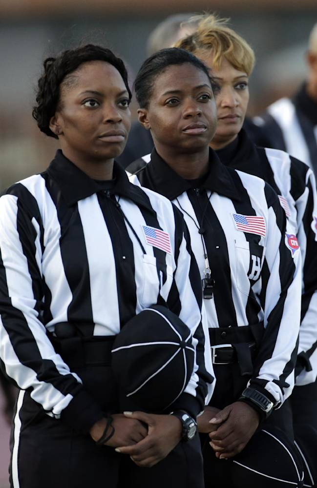 Women referees, from left, line judge Tangela Mitchell, head linesman Yvonda Lewis and field judge Sebrina Brunson stand at attention for the national anthem prior to the start of an NCAA college football game against Lane and Miles in Fairfield, Ala., Thursday, Oct. 24, 2013