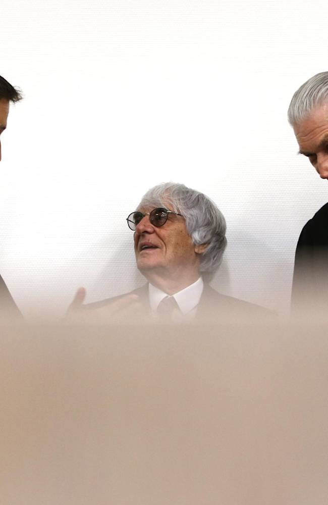 Formula One boss Bernie Ecclestone. center,  stands next to his lawyers Norbert Scharf , left,  and Sven Thomas . right, in  the regional court in Munich on Tuesday June 24, 2014. Ecclestone is charged with bribery and incitement to breach of trust