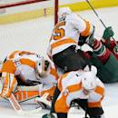 Philadelphia Flyers goalie Ray Emery, left, smothers the puck as teammate Nick Schultz sends Minnesota Wild's Kyle Brodziak, right, to the ice in the first period of an NHL hockey game, Tuesday, Dec. 23, 2014, in St. Paul, Minn. (AP Photo/Jim Mone)