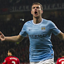 Manchester City's Edin Dzeko celebrates after scoring his second goal against Manchester United during their English Premier League soccer match at Old Trafford Stadium, Manchester, England, Tuesday March 25, 2014