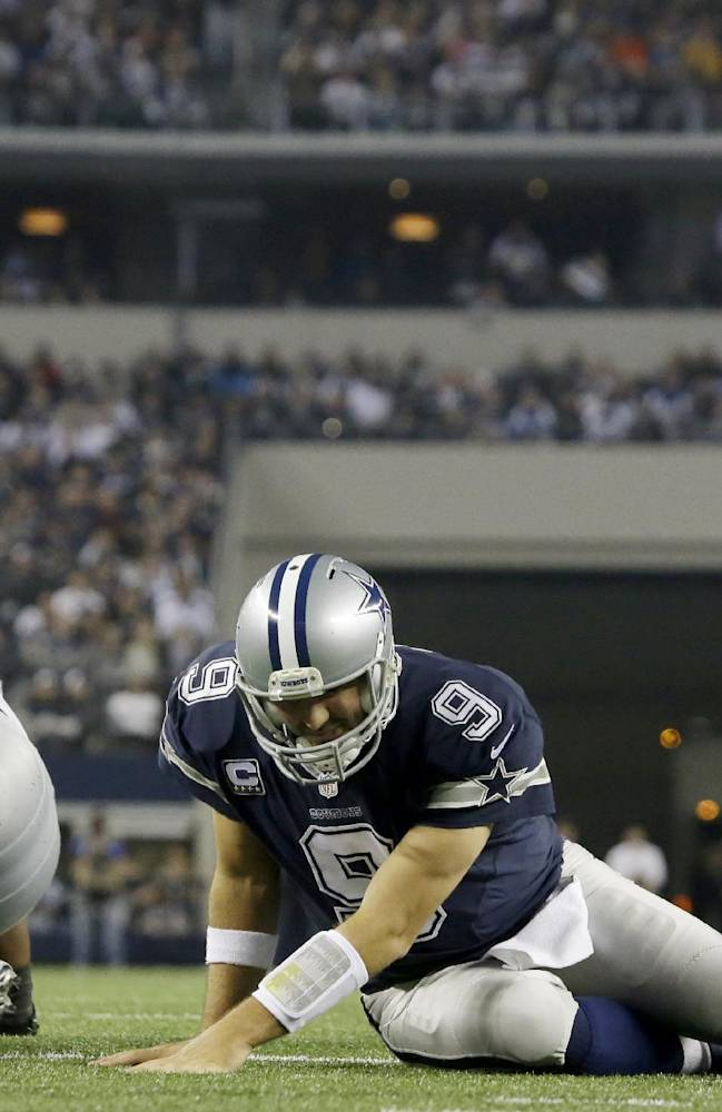Dallas Cowboys quarterback Tony Romo (9) recovers after being sacked by Oakland Raiders defensive tackle Daniel Muir (97) during the second half of an NFL football game, Thursday, Nov. 28, 2013, in Arlington, Texas