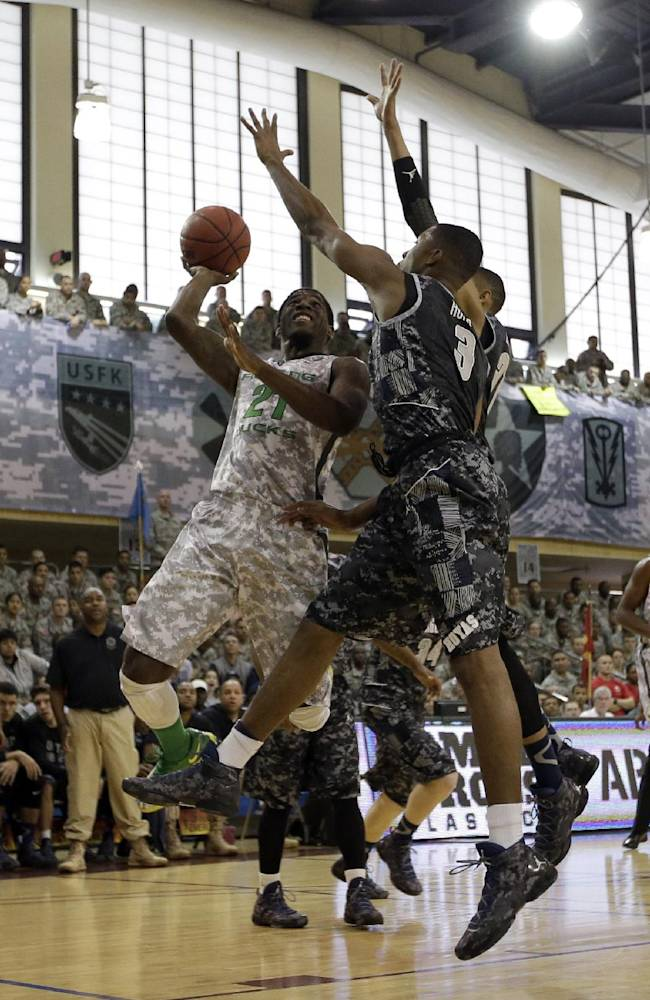 CORRECTS SPELLING OF CITY TO PYEONGTAEK- Oregon's Damyean Dotson (21) is blocked by Georgetown's Mikael Hopkins (3) and Stephen Domingo (31) during the first half of an NCAA college basketball game in the Armed Forces Classic at Camp Humphreys in Pyeongtaek, south of Seoul, South Korea, Saturday, Nov. 9, 2013