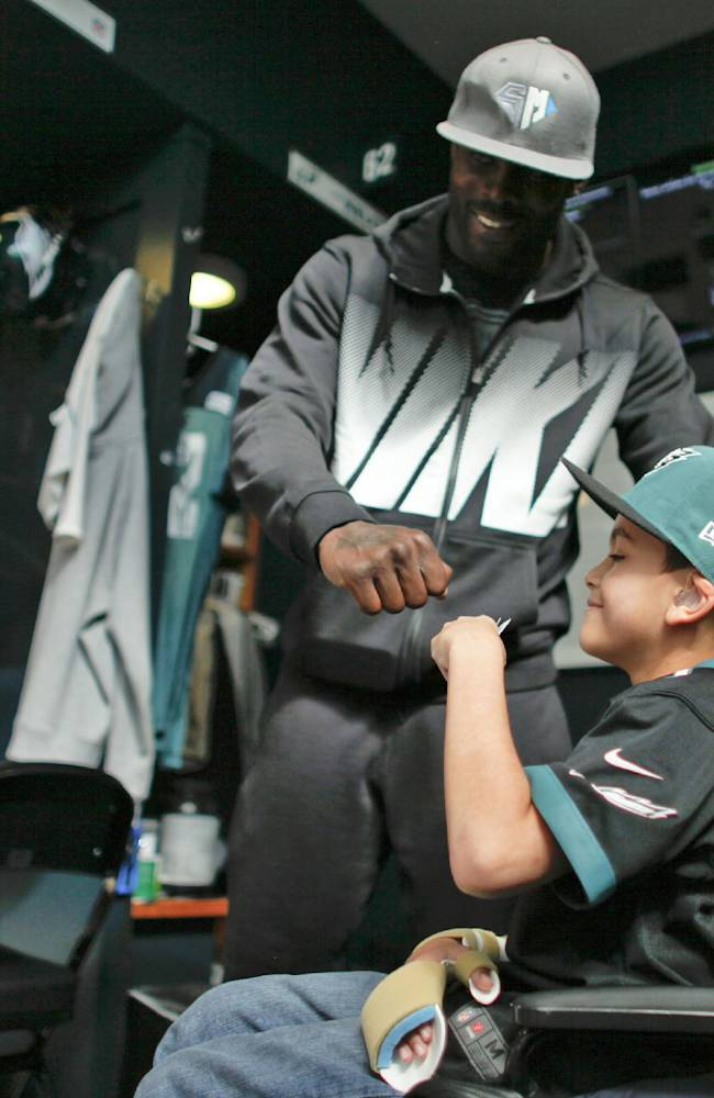 In this Oct. 18, 2013 photo, Philadelphia eagles quarterback Michael Vick give seven-year-old Justin Perales  a fist bump during a tour of the Eagles training facility in Philadelphia. Four years after his release from prison, Vick is one of the NFL's most active players involving charities. Though he's no longer the starting quarterback for the Eagles, he's unquestionably the team leader