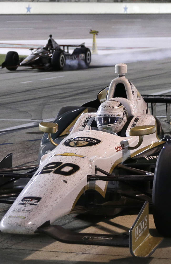 Ed Carpenter (20) pulls in for a pit stop as Will Power, of Australia, locks up his tires while slowing in the background during the IndyCar auto race at Texas Motor Speedway in Fort Worth, Texas, Saturday, June 7, 2014. Power was penalized for speeding on pit row