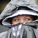 NASCAR fan Rhonda Haffly, of North Augusta, Ga., tries to stay dry as she waits for the Sprint Cup series auto race to begin at Atlanta Motor Speedway Sunday, March 1, 2015, in Hampton, Ga. (AP Photo/ John Amis )