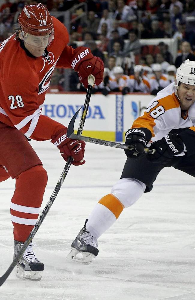 Carolina Hurricanes' Alexander Semin (28), of Russia, shoots as Philadelphia Flyers' Adam Hall (18) defends during the second period of an NHL hockey game in Raleigh, N.C., Tuesday, Nov. 5, 2013