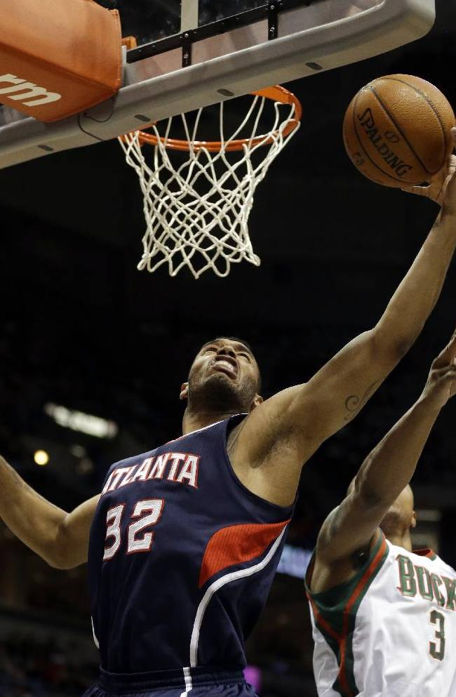 Atlanta Hawks' Mike Scott (32) reaches for a rebound against Milwaukee Bucks' Caron Butler (3) during the first half of an NBA basketball game Saturday, Jan. 25, 2014, in Milwaukee