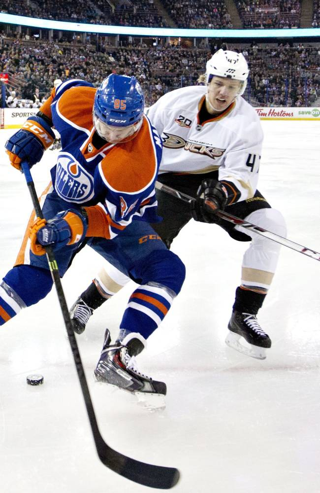 Anaheim Ducks' Hampus Lindholm (47) and Edmonton Oilers' Martin Marincin (85) battle for the puck as Ducks' Ben Lovejoy (6) pursues during first-period NHL hockey game action in Edmonton, Alberta, Friday, March 28, 2014
