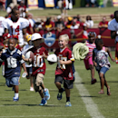 Children run with Washington Redskins receivers Ryan Grant (14), and Rashad Lawrence (17) after practice at the team's NFL football training facility, Friday, July 25, 2014 in Richmond, Va. (AP Photo) The Associated Press