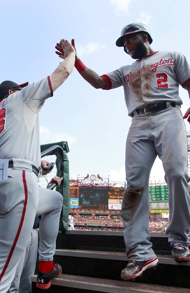 Washington Nationals' Denard Span, right, is congratulated by bench coach Randy Knorr after scoring on a single by Bryce Harper during the first inning of a baseball game against the St. Louis Cardinals Wednesday, Sept. 25, 2013, in St. Louis