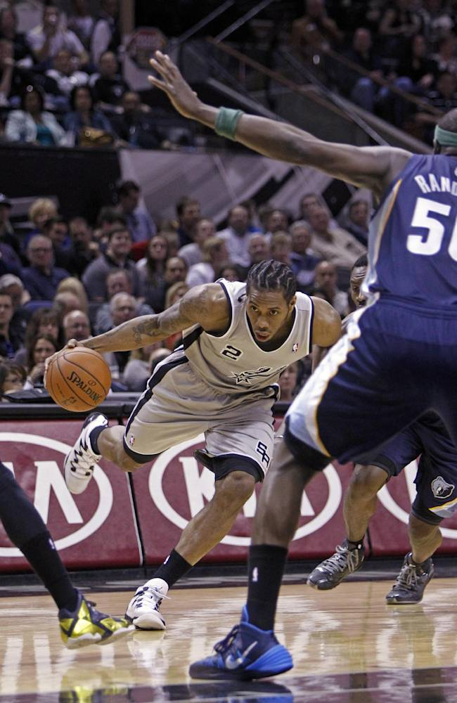 San Antonio Spurs' Kawhi Leonard (2) looks to drive the ball against Memphis Grizzlies' Zach Randolph (50) during the first quarter of an NBA basketball game, Sunday, April 6, 2014, in San Antonio