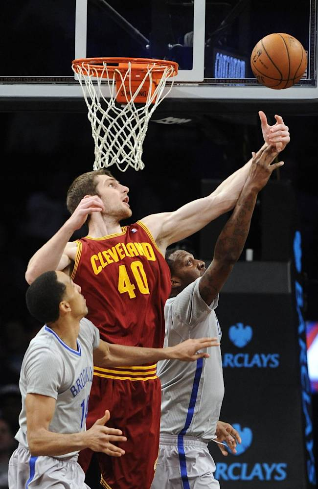 Brooklyn Nets' Shaun Livingston (14) and Andray Blatche, right, vie for a rebound with Cleveland Cavaliers' Tyler Zeller (40) during the first half of an NBA basketball game Friday, March 28, 2014, in New York