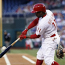 Philadelphia Phillies' Jimmy Rollins connects for an RBI-single, scoring Marlon Byrd from second base during the first inning of a baseball game against the Miami Marlins, Saturday, April 12, 2014, in Philadelphia The Associated Press