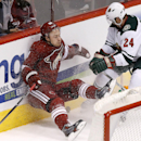 Minnesota Wild's Matt Cooke (24) checks Phoenix Coyotes' Mikkel Boedker, of Denmark, into the boards during the third period of an NHL hockey game, Saturday, March 29, 2014, in Glendale, Ariz. The Wild defeated the Coyotes 3-1 The Associated Press