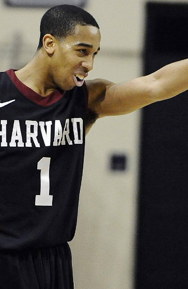 Harvard's Siyani Chambers, points and smiles at his team as he dribbles in the final seconds of an NCAA college basketball game against Yale, Friday, March 7, 2014, in New Haven, Conn. Harvard won 70-58