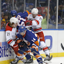 New York Islanders defenseman Thomas Hickey (14) vies for the puck with Carolina Hurricanes left wing Brock McGinn (21) as Hurricanes center Ben Holmstrom (23) checks New York Islanders center Frans Nielsen (51) during the first period of a preseason NHL