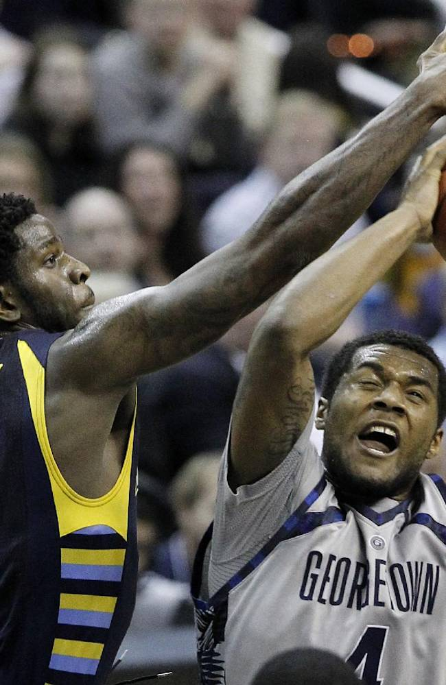 Georgetown guard D'Vauntes Smith-Rivera (4) tries to shoot past Marquette forward Jamil Wilson (0) during the second half of an NCAA college basketball game, Monday, Jan. 20, 2014, in Washington. Marquette won 80-72 in overtime
