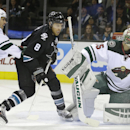 San Jose Sharks' Joe Pavelski (8) takes a shot against Minnesota Wild goalie Darcy Kuemper, right, during the first period of an NHL hockey game Thursday, Dec. 11, 2014, in San Jose, Calif The Associated Press