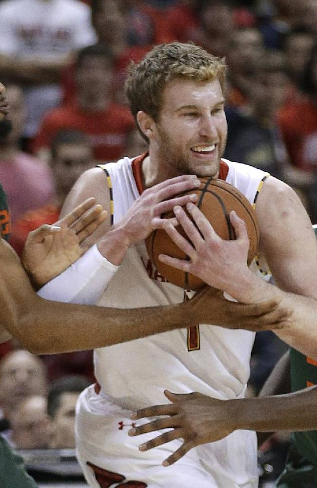 Maryland forward Evan Smotrycz, center, pushes between Miami forward Donnavan Kirk, left, and guard Davon Reed during the second half of an NCAA college basketball game in College Park, Md., Wednesday, Jan. 29, 2014. Smotrycz contributed 15 points to Maryland's 74-71 win