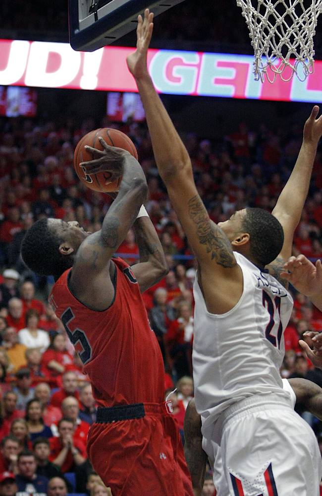 Utah's Delon Wright, left, shoots for two over the attempted defense of Arizona's Brandon Ashley (21) in the second half of an NCAA college basketball game on Sunday, Jan. 26, 2014 in Tucson, Ariz