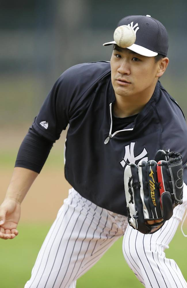 New York Yankees starting pitcher Masahiro Tanaka fields the ball during a drill before an exhibition baseball game against the Pittsburgh Pirates Thursday, Feb. 27, 2014, in Tampa, Fla