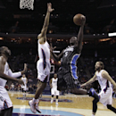 Orlando Magic's Victor Oladipo, center, drives between Charlotte Bobcats' Gerald Henderson, second from left, and Josh McRoberts, second from right, during the first half of an NBA basketball game in Charlotte, N.C., Wednesday, Dec. 11, 2013 The Associate