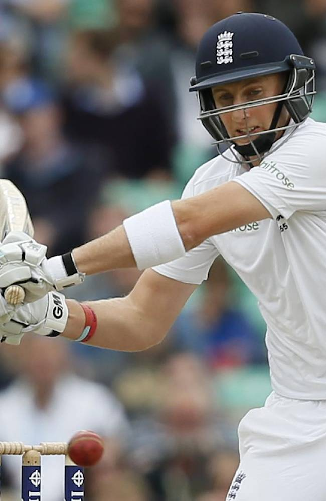 England's Joe Root goes to hit four runs off a ball bowled by India's Ishant Sharma during the third day of the fifth test cricket match at Oval cricket ground in London, Sunday, Aug. 17, 2014