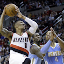 Portland Trail Blazers guard Damian Lillard, left, drives to the basket against Denver Nuggets' Randy Foye, right, and J.J. Hickson during the second half of an NBA basketball game in Portland, Ore., Saturday, March 1, 2014. Lillard scored 17 points as t