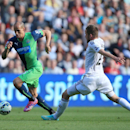 Newcastle United's Gabriel Obertan, left, battles for the ball with Swansea City's Gylfi Sigurdsson during their English Premier League soccer match at the Liberty Stadium, Swansea, Wales, Saturday, Oct. 4, 2014