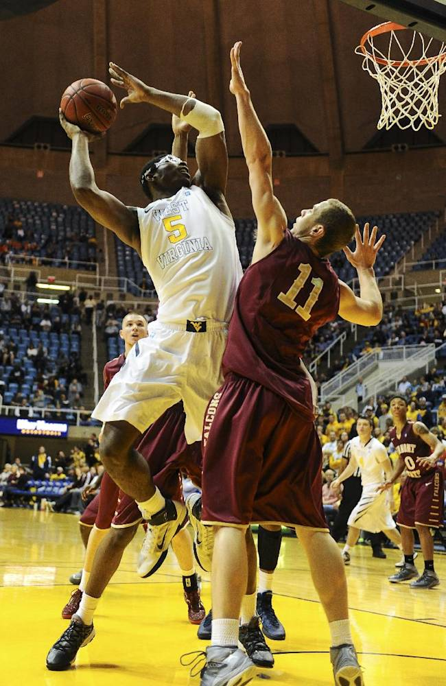 West Virginia's Devin Williams (5) looks to shoot over Brendan Cooper (11) during the second half of an NCAA college basketball exhibition game at WVU Coliseum in Morgantown, W.Va., on Monday, Nov. 4, 2013. West Virginia won 89-70