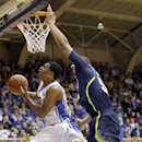 Duke's Quinn Cook drives past Michigan's Jordan Morgan, right, during the second half of an NCAA college basketball game in Durham, N.C., Tuesday, Dec. 3, 2013. Duke won 79-69 The Associated Press