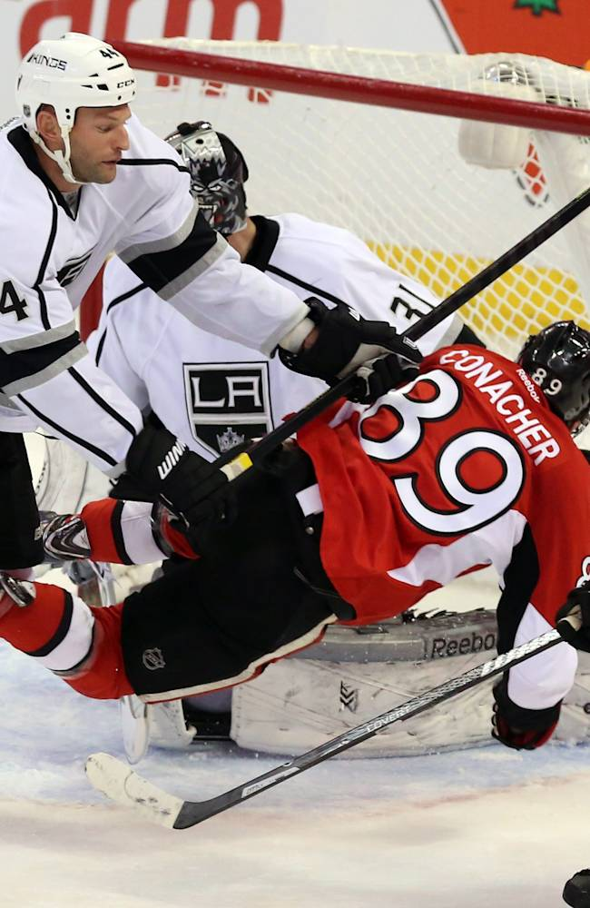 Ottawa Senators' Cory Conacher (89) is checked by Los Angeles King, Robyn Regehr (44) during the second period of an NHL hockey game in Ottawa, Saturday, Dec. 14, 2013
