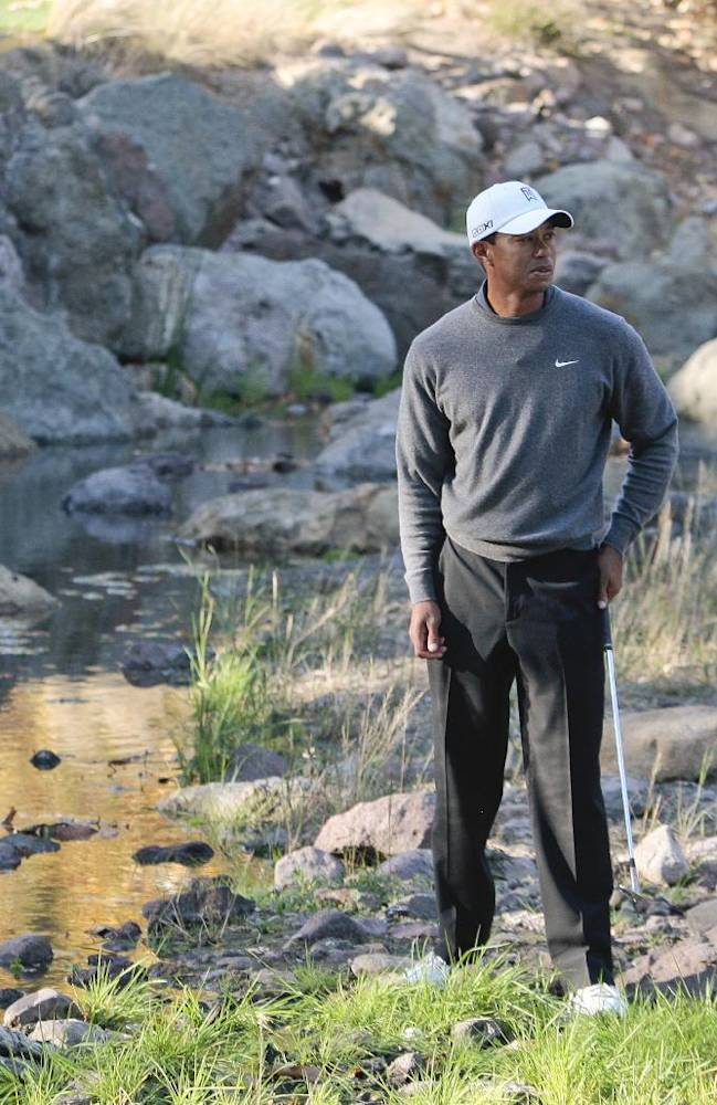 Tiger Woods waits to play a shot from a creek bed to the sixteenth green during the third round of the Chevron World Challenge golf tournament at Sherwood Country Club, Saturday, Dec. 3, 2011, in Thousand Oaks, Calif. Woods took a drop after determining the ball to be unplayable