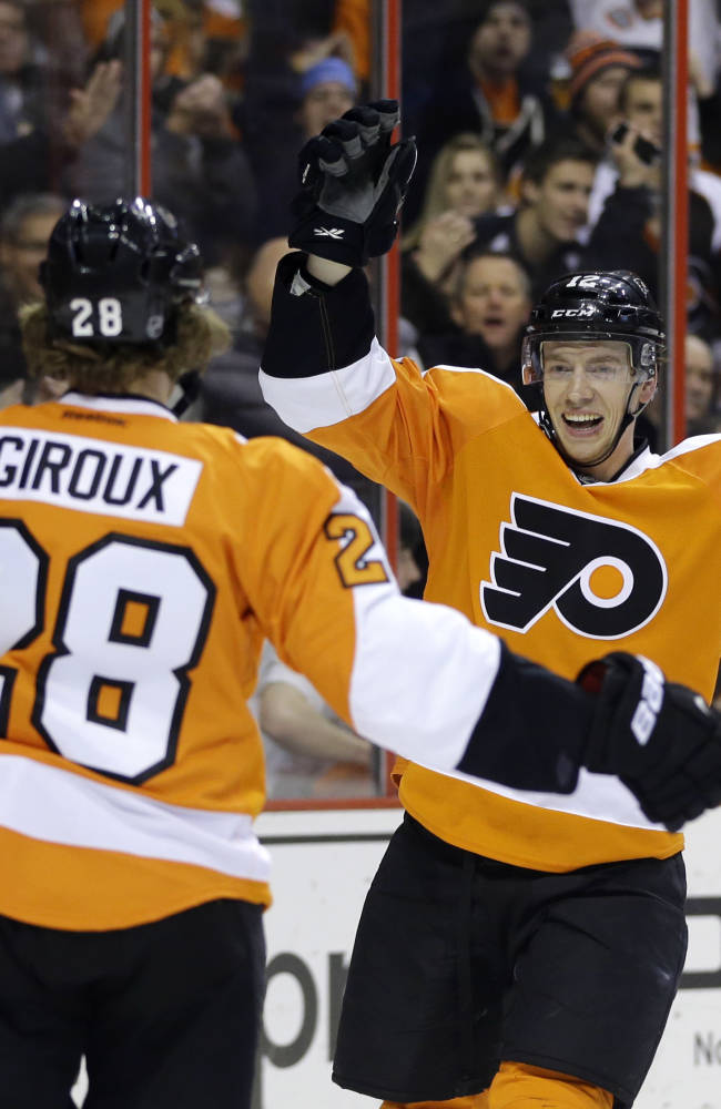 Philadelphia Flyers' Michael Raffl, right, of Austria, celebrates with Claude Giroux after Raffl scored during the second period of an NHL hockey game against the Montreal Canadiens, Wednesday, Jan. 8, 2014, in Philadelphia