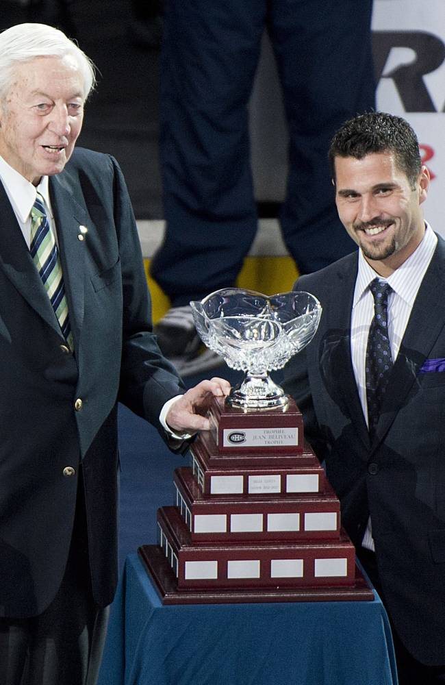 Hockey great Jean Beliveau, left, presents Montreal Canadiens' Brian Gionta with the Jean Beliveau Trophy prior to an NHL preseason hockey game between the Canadiens and the Carolina Hurricanes in Montreal, Saturday, Sept. 21, 2013