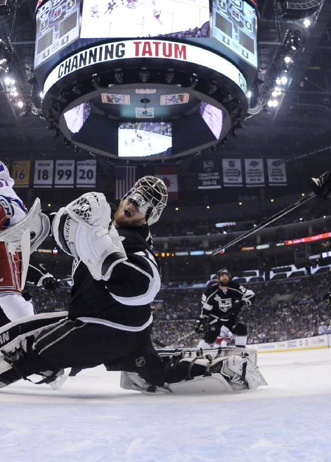 Los Angeles Kings goalie Jonathan Quick, center, collides with New York Rangers left wing Benoit Pouliot, left, during the first period of Game 5 of the NHL Stanley Cup Final series Friday, June 13, 2014, in Los Angeles