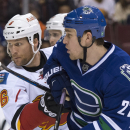 Vancouver Canucks center Shawn Matthias (27) fights for control of the puck with Calgary Flames defenseman Dennis Wideman (6) during the first period of an NHL hockey game Saturday, Jan. 10, 2015, in Vancouver, British Columbia The Associated Press
