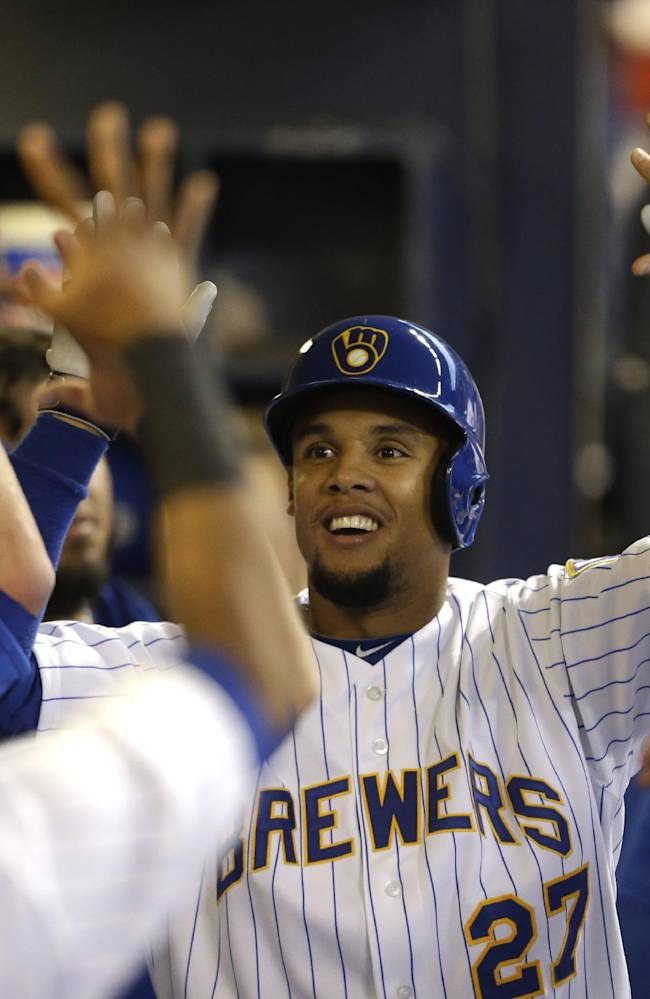 Milwaukee Brewers' Carlos Gomez reacts in the dugout after his home run off Pittsburgh Pirates starting pitcher Edinson Volquez during the first inning of a baseball game Saturday, April 12, 2014, in Milwaukee