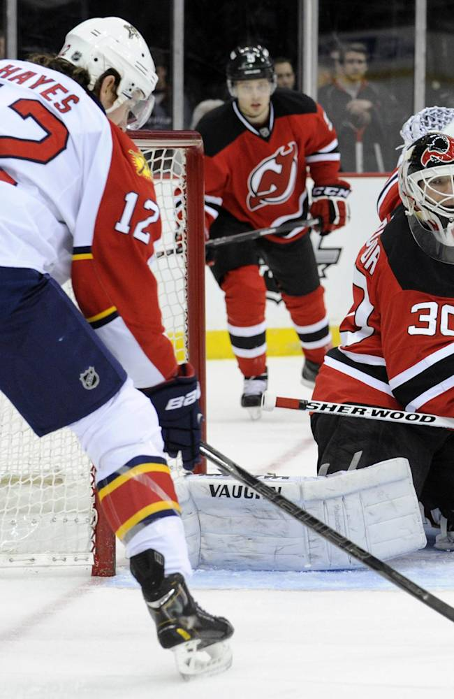 Florida Panthers' Jimmy Hayes, left,  skates in on New Jersey Devils goaltender Martin Brodeur during the first period of an NHL hockey game Monday, March 31, 2014, in Newark, N.J