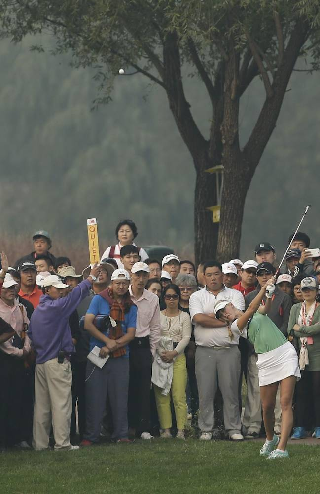 Spectators watch Jessica Korda of the United States driving a ball on the 18th hole during the second round of the Reignwood LPGA Classic golf tournament at Pine Valley Golf Club on the outskirts of Beijing, China, Friday, Oct. 4, 2013