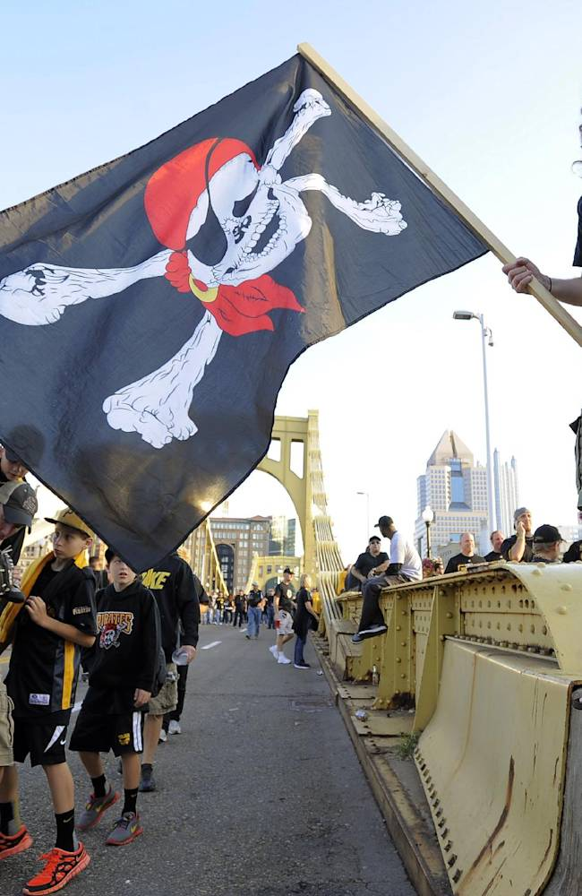 Derek Buck, of Pittsburgh, waves a Jolly Roger flag as he stands on the Roberto Clemente Bridge as fans make their way to the NL wild-card playoff baseball game between the Pittsburgh Pirates and the Cincinnati Reds on Tuesday, Oct. 1, 2013, in Pittsburgh