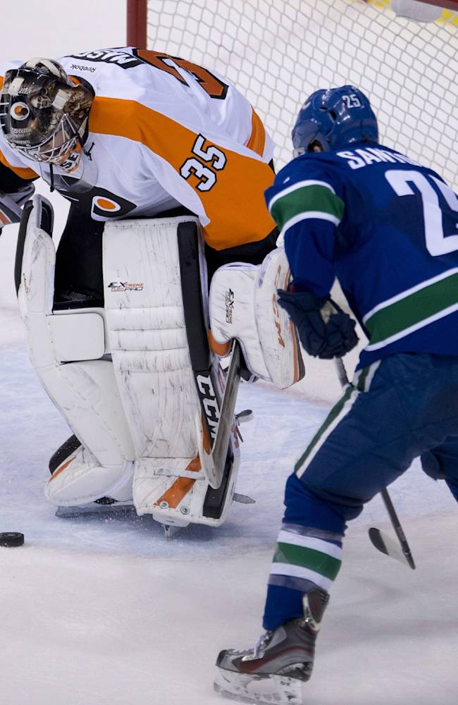 Vancouver Canucks center Mike Santorelli (25) tries to get a shot past Philadelphia Flyers goalie Steve Mason (35) during the second period of an NHL hockey game in Vancouver, British Columbia, Monday, Dec. 30, 2013