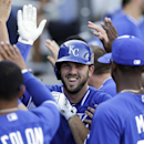 Kansas City Royals' Mike Moustakas, center, is greeted by teammates in the dugout after hitting a three-run home run against the Arizona Diamondbacks during the fifth inning of an exhibition spring training baseball game Wednesday, March 5, 2014, in Scott