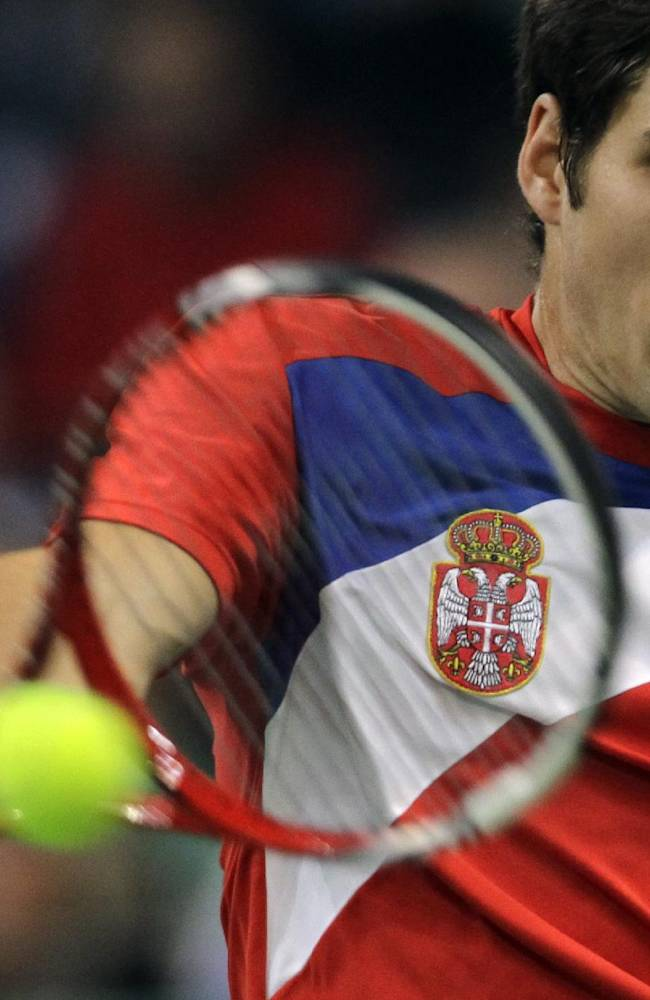 Dusan Lajovic of Serbia returns a ball to Czech Republic's Tomas Berdych during their Davis Cup finals tennis singles match in Belgrade, Serbia, Friday, Nov. 15, 2013