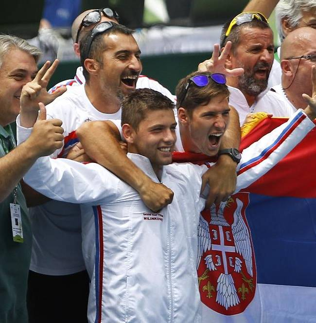 Serbia's Filip Krajinovic, fourth left, celebrates with teammates and support staff after their win over India in the Davis Cup tennis World Group play-off tie between India and Serbia, in Bangalore, India, Monday, Sept. 15, 2014. Krajinovic beat Bhambri in straight sets 6-3, 6-4, 6-4 in the second reverse singles to help Serbia qualify for the World Group of the Davis Cup on Monday