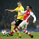 Dortmund's Sven Bender, left, battles for the ball with Arsenal's Santi Cazorla during the Champions League group D soccer match between Arsenal and Borussia Dortmund at the Emirates stadium in London, Wednesday, Nov. 26, 2014