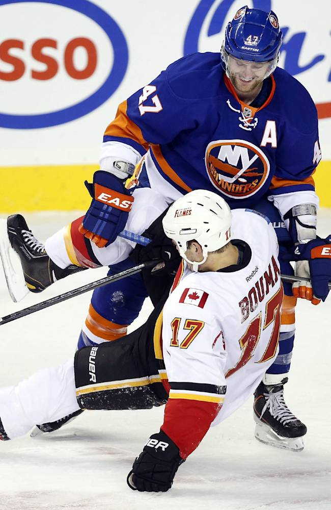 New York Islanders' Andrew Macdonald, right, laughs as he gets his stick caught in the thigh pad of Calgary Flames' Lance Bouma during the first period of a preseason NHL hockey game Tuesday, Sept. 17, 2013, in Calgary, Alberta