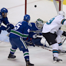 San Jose Sharks center Logan Couture (39) tries to get a shot past Vancouver Canucks goalie Eddie Lack, second from right, as teammates Dane Fox, second from left, and left wing Kellan Lain (54) look on during the first period of an NHL preseason hockey g